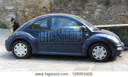 AREZZO ITALY - CIRCA APRIL 2016: blue Volkswagen New Beetle car parked in a street of the city centre