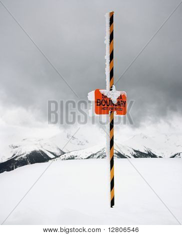 Ski area trail boundary sign in snow-covered mountain scene in Whistler, British Columbia, Canada.