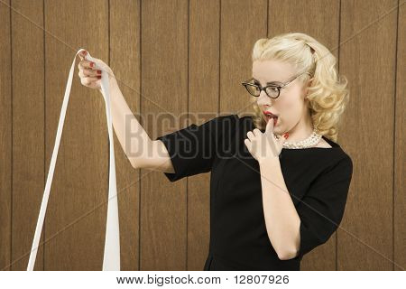 Mid-adult Caucasian female in vintage outfit holding a printout with finger on her lip.