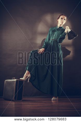 Woman retro style long dark green gown with old suitcase and feather fan vintage photo