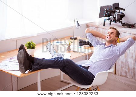 Full of gladness. Pleasant handsome delighted smiling man holding his legs on the surface of table and sitting in the chair while resting