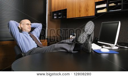 Caucasian middle-aged businessman in office sitting with feet on desk.