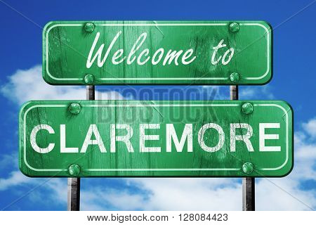 claremore vintage green road sign with blue sky background