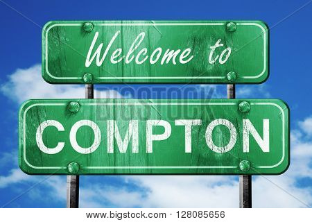 compton vintage green road sign with blue sky background