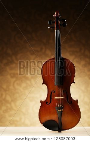 aged handmade violin on bright beige background
