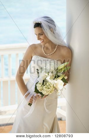 Caucasian mid-adult bride holding bouquet looking down.
