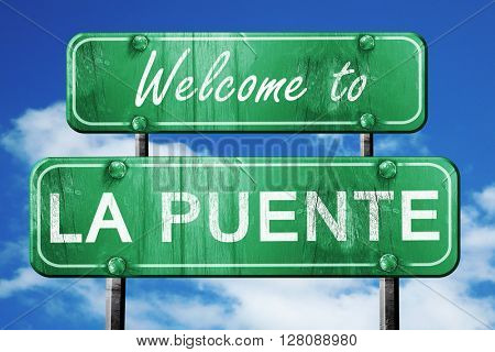 la puente vintage green road sign with blue sky background