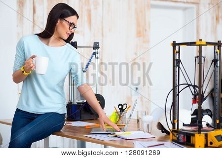 Free minute at work. Cheerful beautiful woman sitting on the table and using laptop while d printer standing in the background