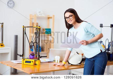 Full of ideas. Positive beautiful smiling woman holding papers and leaning on the table while 3d printer working nearby