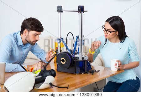 Concentrate on work. Pleasant serious involved colleagues sitting at the table and working with 3d printer
