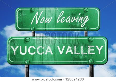 Leaving yucca valley, green vintage road sign with rough letteri
