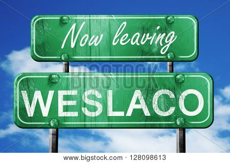 Leaving weslaco, green vintage road sign with rough lettering