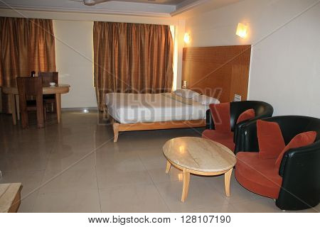 Interior of a room containing cushioned chairs tea table bed dining table and window curtains