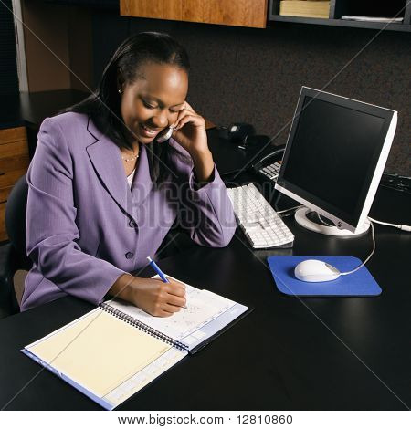 High angle view of African-American young adult business woman talking on cell phone and writing in planner in office.