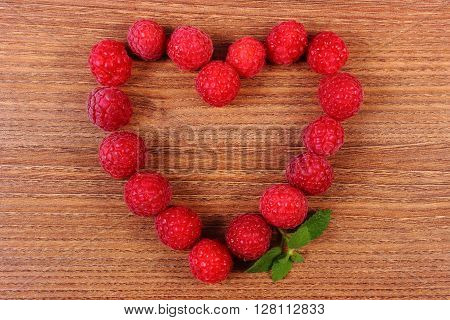 Heart shaped fresh raspberries on wooden table healthy food and dessert symbol of love