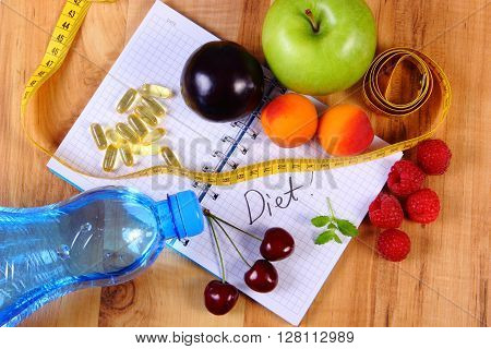 Fruits with mineral water tape measure and tablets supplements on notebook for writing notes choice between healthy eating and slimming pills