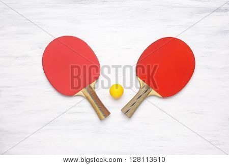 Two table tennis rackets on a white wooden table. Top view of ping pong paddles. Competition concept.