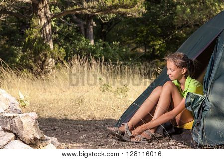 Woman in a tent and puts on the shoe on her leg