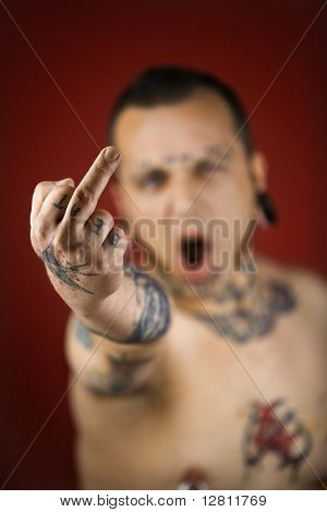 Caucasian mid-adult man with tattoos and piercings holding up middle finger.