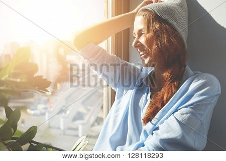 Happy Young Female Artist Contemplating Urban Landscape Through The Window, Smiling In Delight While