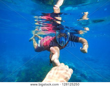 Couple holding hands, life underwater near the coral reef, man snorkeling in mask, freediving sport activity, sportsman underwater, diving in warm sea, snorkels in the blue sea, snorkeling in water