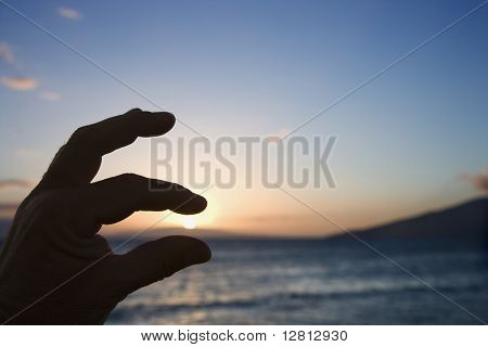 Hand in foreground with fingers around sunrise over the coast of Kihei, Maui, Hawaii, USA.