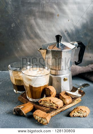 Glass of latte coffee on rustic wooden board, cantucci biscuits and steel Italian Moka pot, grey background, selective focus