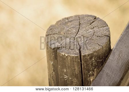 part of an old column from a wooden fence for the ranch closeup on an indistinct background of color sepia