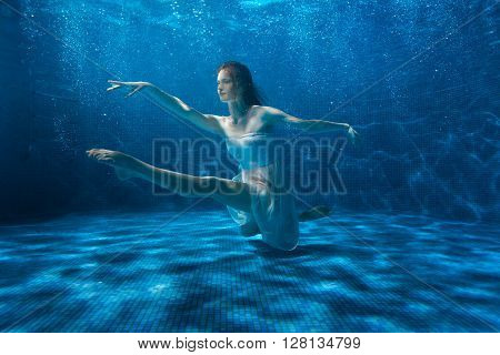 Woman posing under the water she dances.