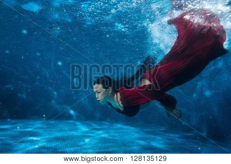 Woman in red dress dives under water in the pool.