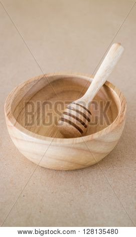 Wooden bowl and dipper on brown background, stock photo
