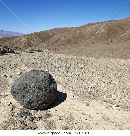 Boulder in barren landscape in Death Valley National Park.