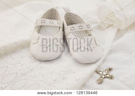 Baby christening white shoes with cross on white lace background