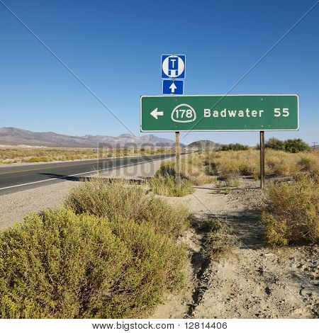Road sign on side of desert road with direction to Badwater, Death Valley.