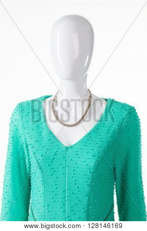 Turquoise dress and silver necklace. Female mannequin wearing precious jewelry. V-neck dress with silver accessory. Woman's bright garment and necklace.