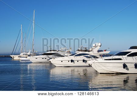 White yachts in the port. On the sea is calm.