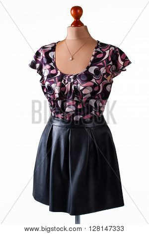 Casual blouse and black skirt. Skirt and blouse on mannequin. Leather skirt with stylish top. Girl's casual outfit and accessory.