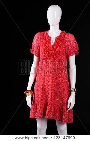 Red casual dress with v-neck. Summer dress on white mannequin. Bright clothes on dark background. Lady's clothing of new design.