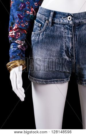 Denim shorts and gold bracelet. Shorts and bracelet on mannequin. Girl's fashionable bracelet on display. Expensive accessory at fair price.