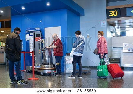 VALENCIA, SPAIN - APRIL 30, 2016: An airline passenger having his luggage wrapped in industrial strength cling film. Wrapping luggage in cling film can provide peace of mind during a journey.