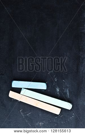 three pieces of chalk over a blackboard