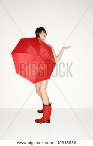 Young sexy Caucasian woman in red boots holding red umbrella and checking for raindrops.