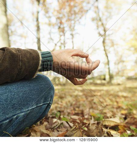 Caucasian man sitting on ground meditating in rural setting.