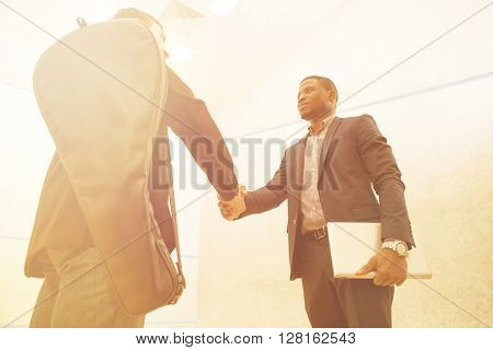 Businessmen shaking hands before having match in squash. Happy men in buiness suits are going to have competition on court. ** Note: Shallow depth of field