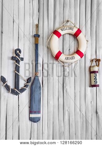 Composition on the marine theme with anchor, paddle and lifeline on old wooden background