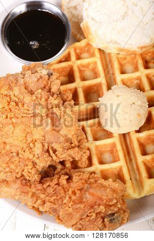 Southern fried chicken and waffles with a country biscuit, honey maple butter and maple syrup