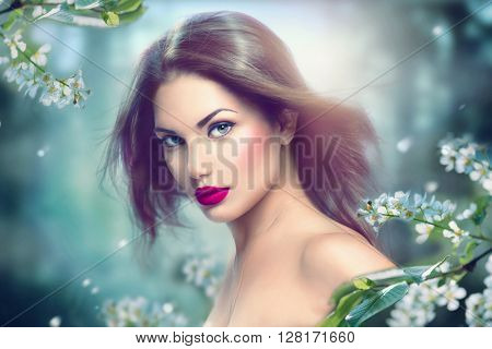 Fashion Spring Model Girl Portrait with Long Blowing Hair. Sexy Glamour Summer Beautiful Woman with Healthy and Beauty Brown Hair with flowers over nature blurred background. Fairy