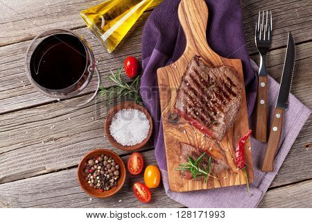 Grilled beef steak with rosemary, salt and pepper and red wine on wooden table. Top view