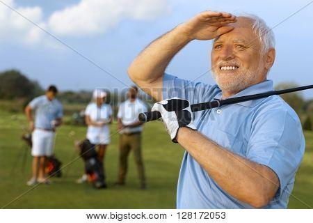 Closeup portrait of elderly male golfer, holding golf club, following shot.