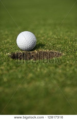 Close up image of golf ball close to the hole.